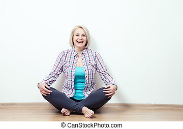 Happy woman sitting on floor with crossed legs.