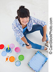 Happy woman sitting on floor with paint
