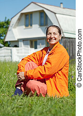 Happy woman sitting on lawn in front of home