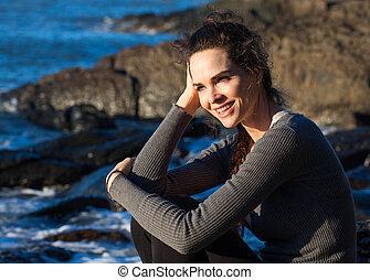 Happy woman sitting on the coast