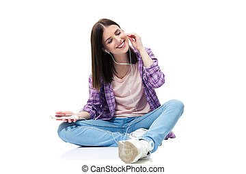 Happy woman sitting on the floor and listening music