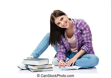 Happy woman sitting on the floor and writing in notebook