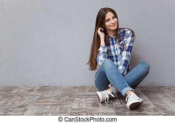 Happy woman sitting on the floor
