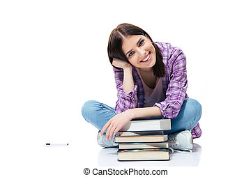 Happy woman sitting on the floor with books