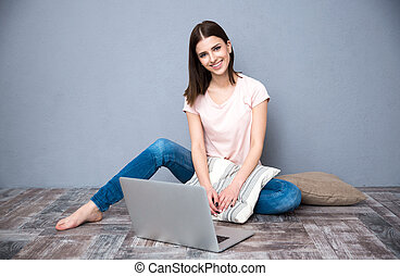 Happy woman sitting on the floor with laptop