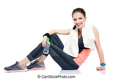 Happy woman sitting on the floor with bottle of water