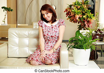 Happy woman sitting on the sofa at home
