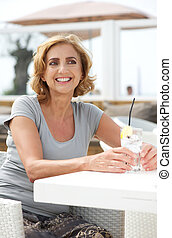 Happy woman sitting with a drink of water