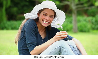 Happy woman smelling a white flower in a park