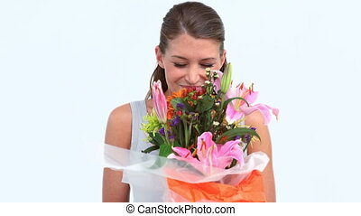 Happy woman smelling beautiful flowers against white...