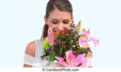 Happy woman smelling flowers against white background