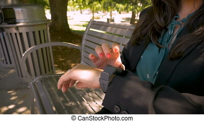 Happy woman smiling and tapping her smart watch while sitting outside