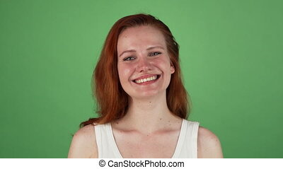 Happy woman smiling, celebrating success on green background...