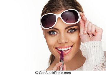happy woman smoking e-cigarette wearing sunglasses