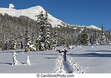 Happy woman snowshoeing in scenic winter landscape