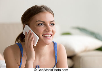 Happy woman speaking on mobile phone at home