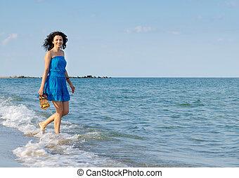 Happy woman splashing through the surf
