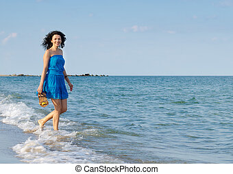 Happy woman splashing through the surf