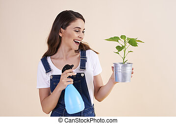 Happy woman spraying the plants with insecticide spray