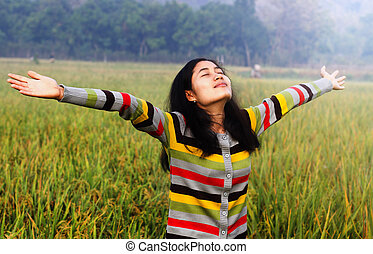 Happy woman spreading hands standing in rice field