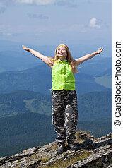 happy woman standing at mountain peak