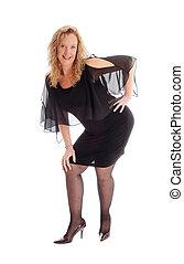 Happy woman standing in a black dress.