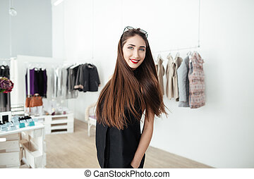 Happy woman standing in clothing store