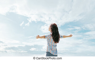Happy woman standing in front of sky.