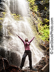 Happy woman standing in front of waterfall