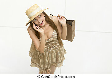 Happy woman standing in shopping centre talking on the phone