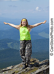 happy woman standing mountain peak