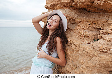 Happy woman standing near the rock on the beach