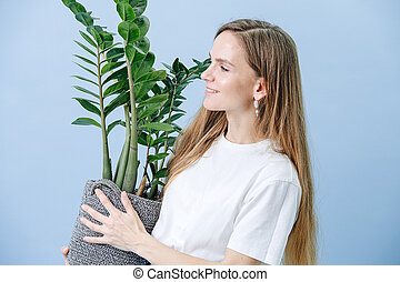 Happy woman standing with a plant in a wicker pot