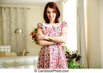 Happy woman standing with arms folded at home