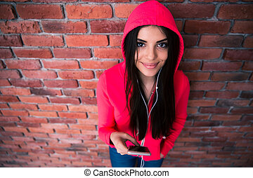 Happy woman standing with smartphone