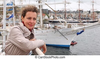 Happy woman stands against set of masts of sailing vessels