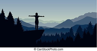 happy woman stands on a cliff in the forest with mountain view nature landscape