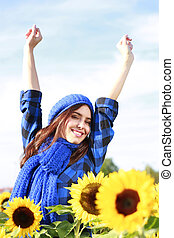Happy woman stretches her arms in a sunflower field