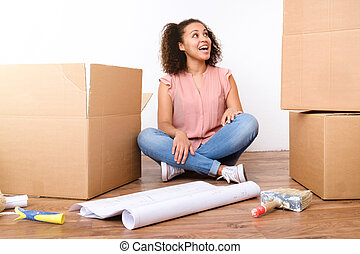 Happy woman surrounded by large boxes