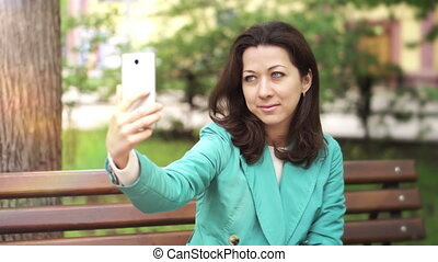 Happy woman taking a selfie on a bench in a park