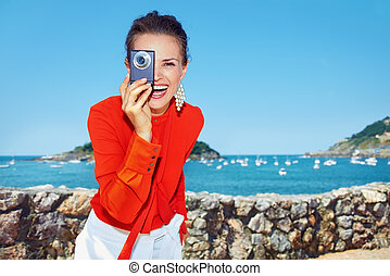 Happy woman taking photo with digital camera in front of lagoon