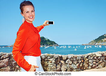 Happy woman taking photo with smartphone of lagoon with yachts