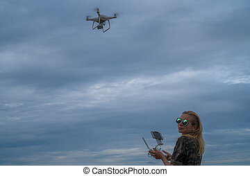 Happy woman standing with remote controller of drone over cloudy sky background