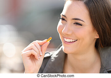 Happy woman taking vitamin pill outdoor