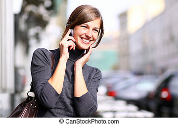 Happy woman talking on cell phone - Young beautiful woman...
