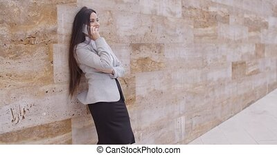 Happy woman talking on phone and leaning on wall