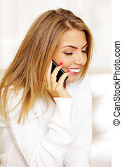Happy woman talking on phone at home