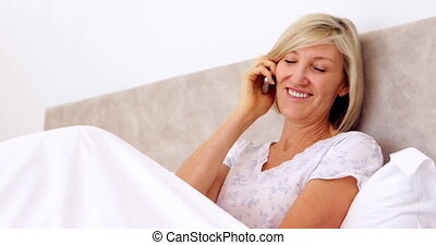Happy woman talking on phone in bed
