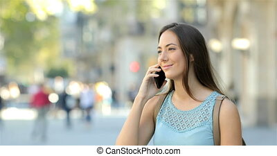 Happy woman talking on phone in the street
