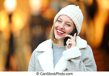 Happy woman talking on phone in winter in a mall